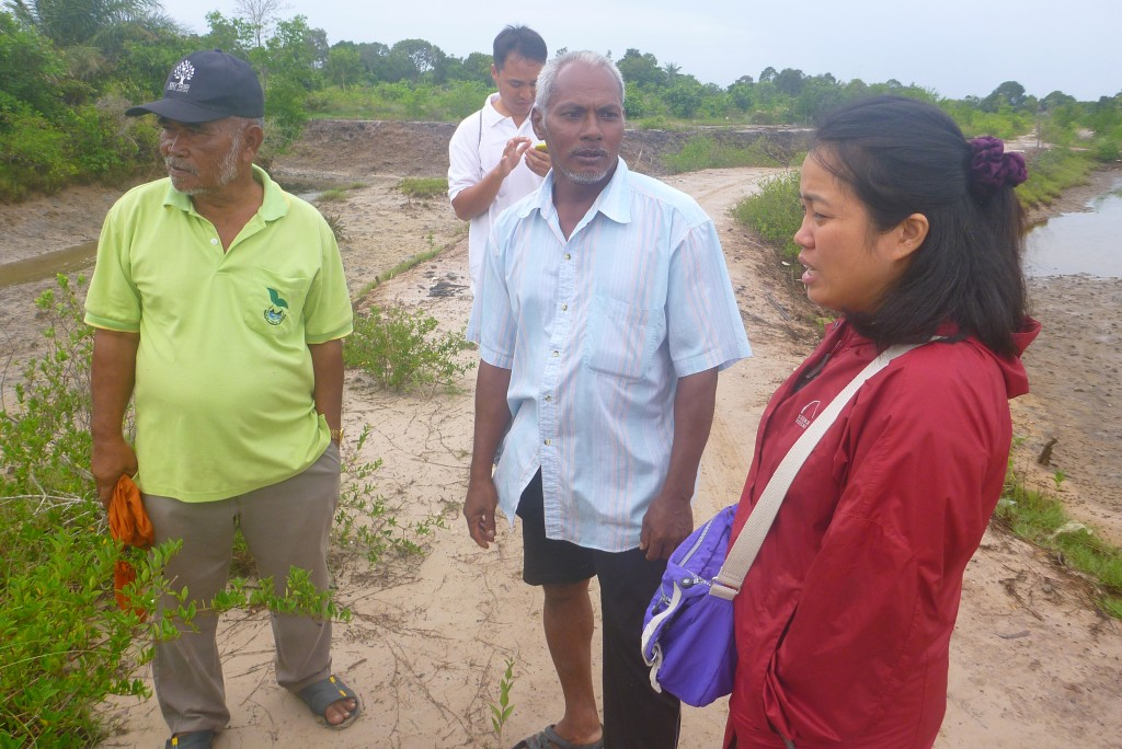 MAP staff person, Jaruwan Enright, discusses pond excavation work with community members at site.